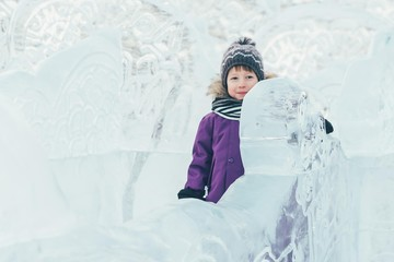 A boy in winter clothes at the ice sculptures