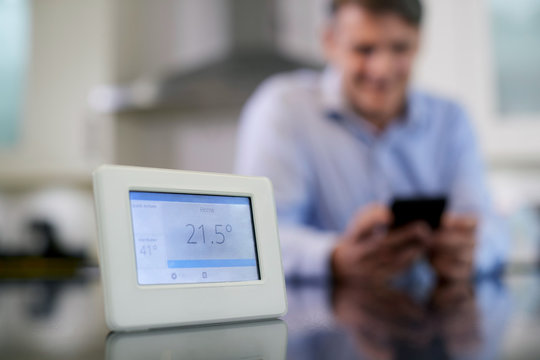Man Controlling Central Heating Smart Meter Using App On Mobile Phone