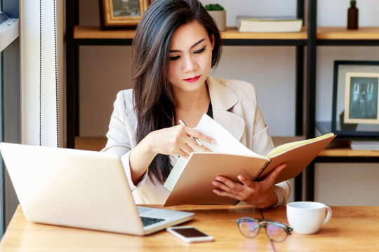 young Asian business woman working at workplace. beautiful Asian woman in casual suit working with reading book, prepare for meeting or interview in modern office. freelance, start up business in Asia