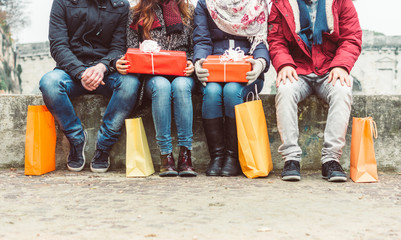 Group of friends sitting outdoor with shopping bags