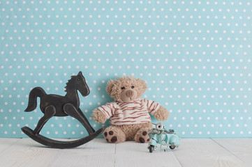 Old wooden toy horse rocking chair, teddy bear and blue vintage motorcycle in baby's room