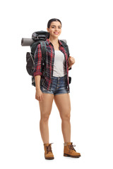 Female hiker with backpack standing and looking at the camera