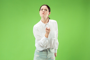 Angry woman looking at camera. Aggressive business woman standing isolated on trendy green studio background. Female half-length portrait. Human emotions, facial expression concept