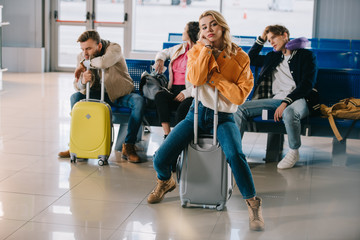 bored young people with luggage waiting for flight in airport terminal