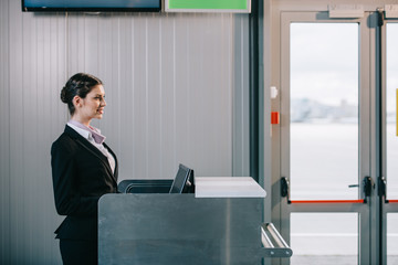 side view of beautiful young female worker at check-in desk in airport