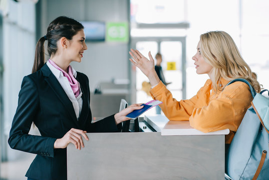 smiling airport worker checking documents of young female traveler at check-in desk