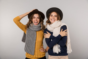 Image of two adorable women wearing hats and scarfs smiling at camera, isolated over gray background