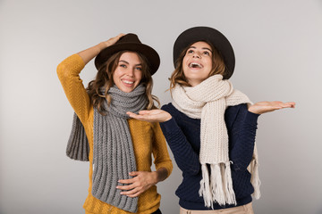 Image of two teenage women wearing hats and scarfs smiling at camera, isolated over gray background