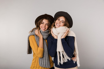 Image of two pleased girls wearing hats and scarfs smiling at camera, isolated over gray background