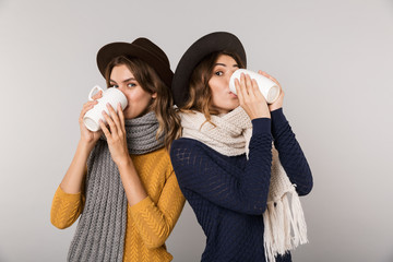 Image of two brunette women wearing hats and scarfs drinking hot tea from cups isolated over gray background