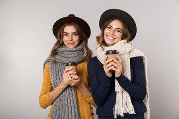 Image of two caucasian women wearing hats and scarfs holding takeaway coffee in paper cups, isolated over gray background
