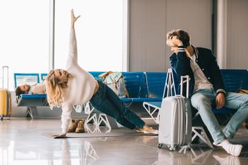beautiful girl practicing yoga while waiting flight in airport terminal