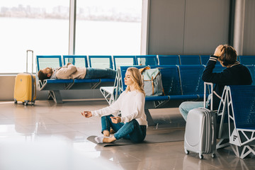 young woman meditating in lotus position while waiting flight in airport terminal