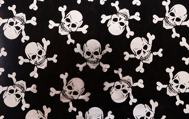 Texture of skulls and bones on dark background. The skulls are used in the Halloween celebration.