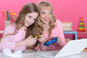 Portrait of beautiful happy mother and daughter playing game