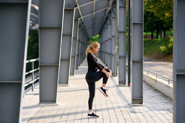 Side view of young blonde woman in sportswear doing stretching exercises outdoors near the stadium. Urban background. Sport concept