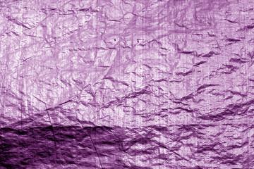Crumpled transparent plastic  surface in purple color.