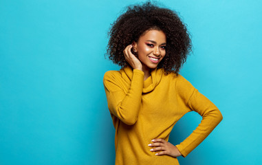 Wall Mural - Smiling black woman with copy space wear yellow cardigan isolated on blue background
