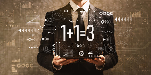 1 plus 1 equal 3 with businessman holding a tablet computer on a dark vintage background