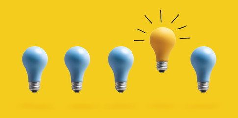 Wall Mural - One outstanding idea concept with light bulbs on a yellow background