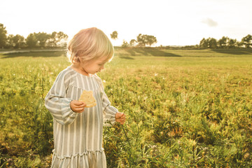Little girl eating in the field