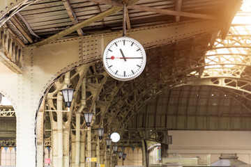 Vintage clock on train station with building roof.