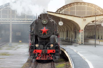 Retro steam train departs from the railway station with the clock on the platform.