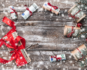Xmas background of old wood. Christmas tree with American and European money. Holiday Gifts. Top view. Space for text. Effect snowflakes.