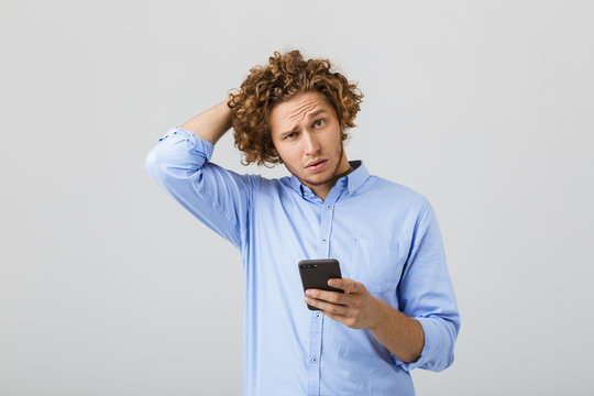 Portrait of a pensive confused young man with curly hair