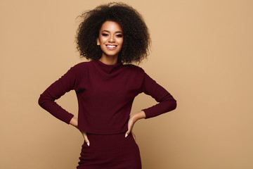 Wall Mural - Beautiful smiling african american woman with an afro hairstyle isolated on studio background with copy space