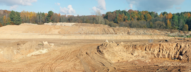 A large hills and pits of sand and traces of a heavy bulldozer  and tractors on a autumn forest  construction site