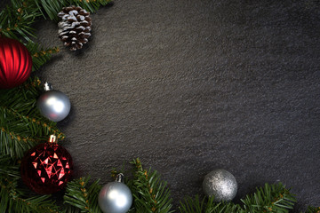 Christmas decoration on dark grey textured background. Ornaments arranged creatively around the borders with fir leaves. Seasons greetings. Flat lay or top view.