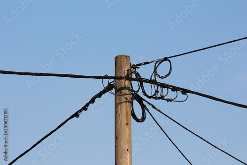 Concrete utility pole with multiple black electrical wires