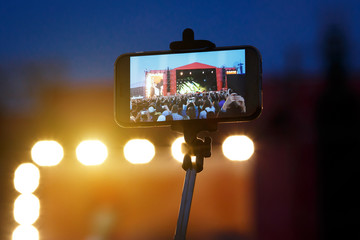 Smartphone on selfie monopod stick. Concert background