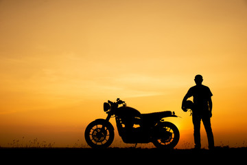 Silhouette of Biker,motorbike parking with sunset background in Thailand.Young Traveller man standing and holding helmet beside motorcycle.Trip and lifestyle of motorbike concept