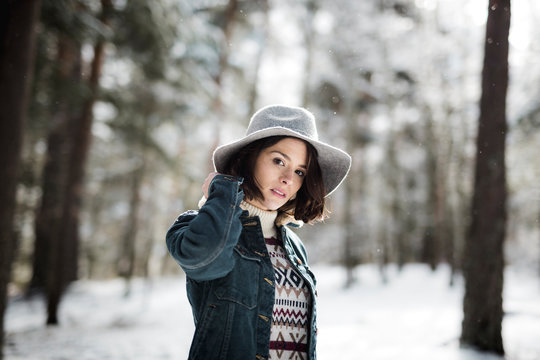 Young woman standing near trees in winter