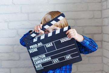 Little boy holds clapper board