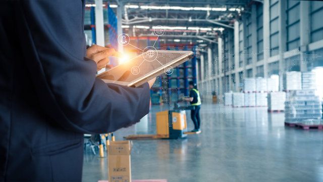 Businessman manager using tablet check and control for workers with Modern Trade warehouse global business commerce concept or import-export commercial logistic. Industry 4.0 concept