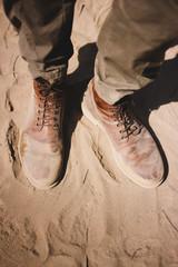 Crop legs standing on sand