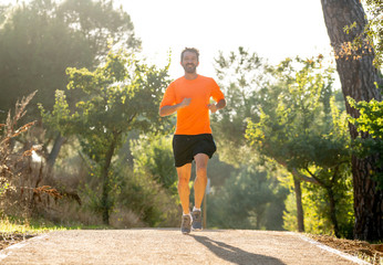 Athletic young man running in the nature at sunset in autumn in fitness Healthy lifestyle