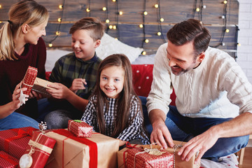 Happy children opening christmas present with parents