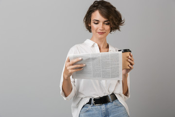 Young woman posing isolated over grey background drinking coffee holding newspaper reading.