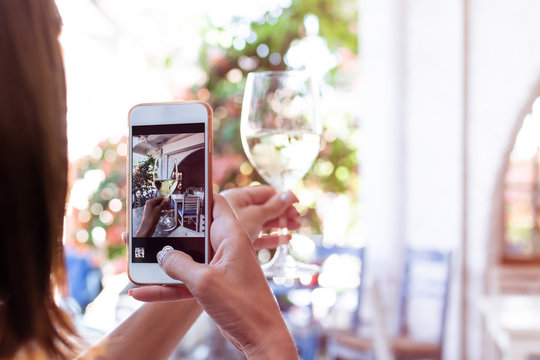 Woman taking photo of white wine on her smartphone in restaurant. Bali island.