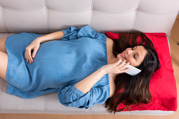 Top view photo of a beautiful smiling pregnant woman in an elegant blue dress while lying on a sofa and talking on her phone.