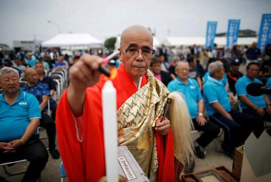 A Buddhist monk performs a ritual prayer for a good catch and safe navigation before the squid fishing ships depart from a port in Sakata