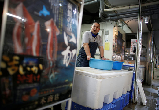 Atsushi Kobayashi, a live squid trader, stands at his shop in Ota Wholesale Market in Tokyo
