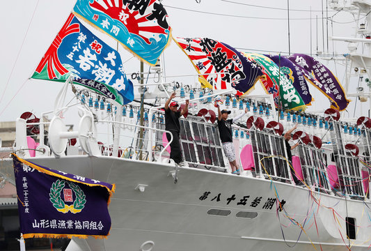 Crew members of the squid fishing ship Wakashio-Maru No.85 wave to relatives as they depart from the port in Sakata