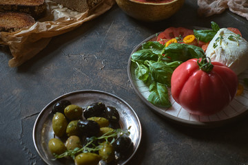 Fresh vegetable and mozzarella salad, toasted farm bread, fresh olives and vegetables. Still life in a rustic style. Healthy and environmentally friendly food. Farm products. Healthy lifestyle.