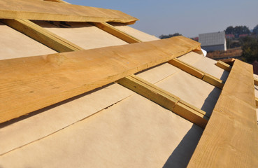 Roofing Construction. Wooden rafters, eaves, waterproofing membrane, logs and timber on house roof corner