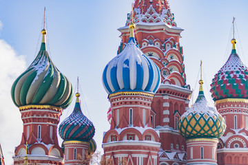 Domes of St Basil's Cathedral covered with snow on blue sky background